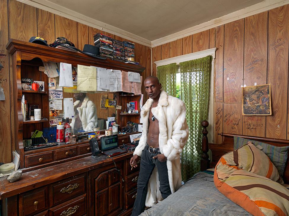 Robert a hálószobájában, Northwest Side, Detroit, 2011 Robert szabadúszó zenei producer. Detroit, a híres Motown, a négynegyedes technó őshazája valaha az amerikai zene fellegvára is volt, de Robertnek mostanában kevés dolga akad. Most elhunyt szülei házában él, ahol se víz, se fűtés, a villanyt is a közvilágításról kötötte le. Télen Los Angelesben csövezett. Mielőtt elutazott, bedeszkázta a földszinti ablakokat, de ezzel csak felkeltette a fosztogatók figyelmét, akik kipakolták és feldúlták otthonát. Még a rézcsöveket is kitépték a falból. A víz elárasztotta a pincét, ráadásul még a 4000 dolláros fogyasztást is kiszámlázta neki a városi vízmű.