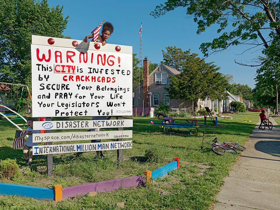 """A Rúzzsal Rajzolt Tábla a Caledonia Street és az Eight Mile Road találkozásánál, Detroit, 2011 A város egyik sajátos nevezetességévé vált táblát egy helyi lakos, Andre Ventura készítette azután, hogy a játszótér közelében lövöldözés volt. Azt mondta, hallani lehetett, ahogy a golyók fütyülnek a fejük fölött, ezért írta ki, hogy """"Figyelem! A várost crackkokainisták lepték el! Vigyázzon értékeire és imádkozzon az életéért, mert az önkormányzat semmit nem tesz a védelmében!"""". A tábla a média figyelmét is felkeltette. Andre azóta még 250 hasonló táblát helyezett el városszerte."""