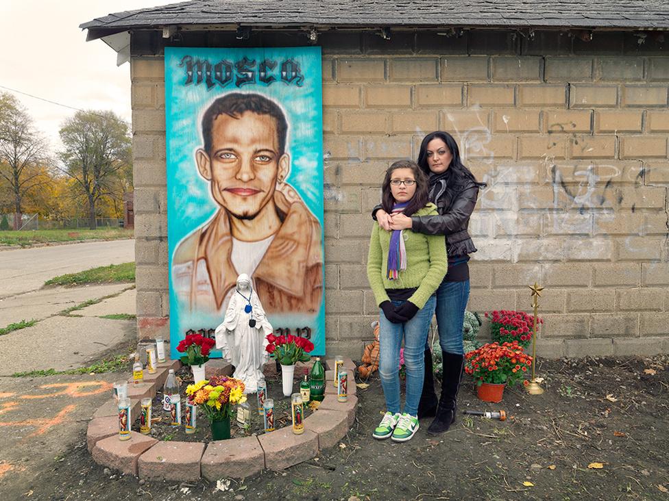 Staces és Carlitha Jason emlékművénél, Southwest Side, Detroit, 2012 Jasont, akit Moscóként is ismertek. 2012 augusztusában gyilkolták meg. Egy gyilkosság szemtanúja volt, a tettes veszélyesnek tartotta magára, ezért felkutatta, és négyszer mellkason lőtte. A haldokló Jason ehhez a házfalhoz kúszott, itt vérzett el. De még halála előtt el tudta árulni a rendőröknek a támadója nevét, aki most mindkét gyilkosságért a bíróság előtt felelhet. Carlitha Jason lánya, akit Stacey, Jason nővére nevel kilenc éve, amikor anyja elhagyta Jasont. Carlitha tizenhárom éve minden szenvedése ellenére jólnevelt, normális gyerek, írja Jordano, aki szerint ez biztos Stacey és Jason szeretetén is múlt.