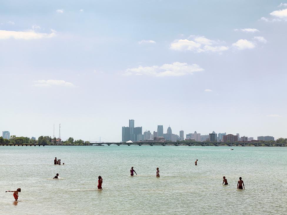 Fürdőzők a Belle Isle szigeten, Kanada és az Egyesült Államok határán a Detroit-folyón, Detroit, 2010 Az ipar összeomlásának vannak pozitív hatásai is. Az egykor súlyosan szennyezett Detroit-folyó egy évtized alatt újra fürödhetővé vált, és még a halak is visszaköltöztek bele. Ötven év után hódokat is láttak már a partján.