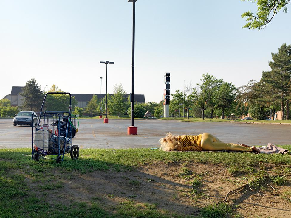 Alvó nő egy parkolóban az East Warren Avenue-n, Detroit, 2010 A hajléktalanság sok nagyvárosban probléma. Detroitban sok szükségszállás van, de sokan nem tudnak vagy akarnak beköltözni. Van, hogy elmebaj miatt, van, hogy nem bíznak a helyekben, esetleg antiszociálisak. És az is előfordul, hogy a hajléktalanság a lényük részévé válik, és már semmi sem tud változtatni választásukon, hogy az utcán éljenek, írja Jordano.