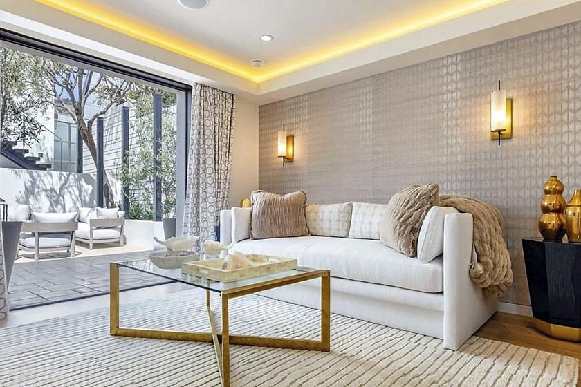 A nappalinak ebből a szegletéből azonnal látható, hogy a fehér, az arany és a natúr színek dominálnak. A helyiségből kényelmesen megközelíthető a terasz.
