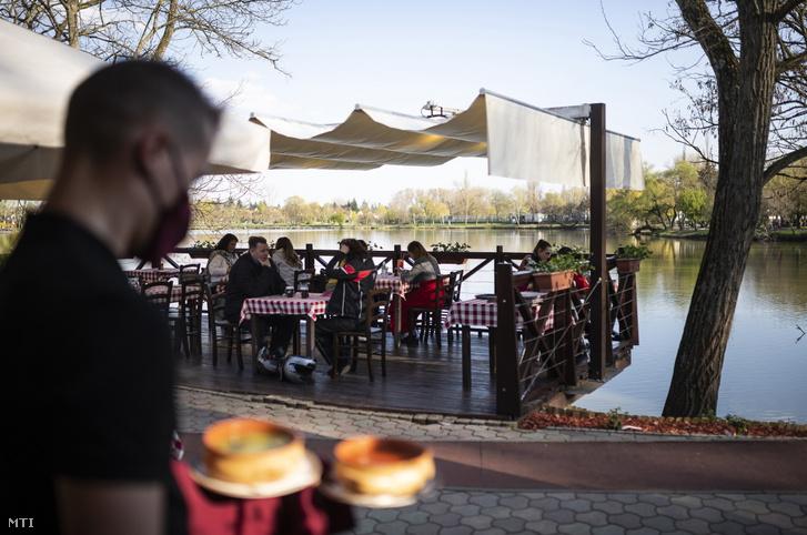 Vendégek ülnek egy étterem teraszán Nyíregyháza-Sóstógyógyfürdőn 2021. április 24-én