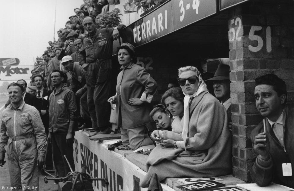 1956, Brit Nagydíj Silverstone-ban. Andrea, a későbbi ötszörös világbajnok Juan-Manuel Fangio barátnője térdelve követi az eseményeket. Fangio győzött aznap.
