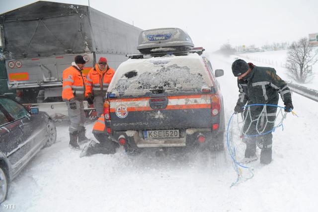 Hóláncot szerelnek a Pest Megyei Kutató-Mentő Szolgálat autójára az M7-es autópályán 2013. március 15-én. A mentőszolgálat dolgozói Fejér megyébe indultak, hogy elakadt mentőket mentsenek ki a hó fogságából.