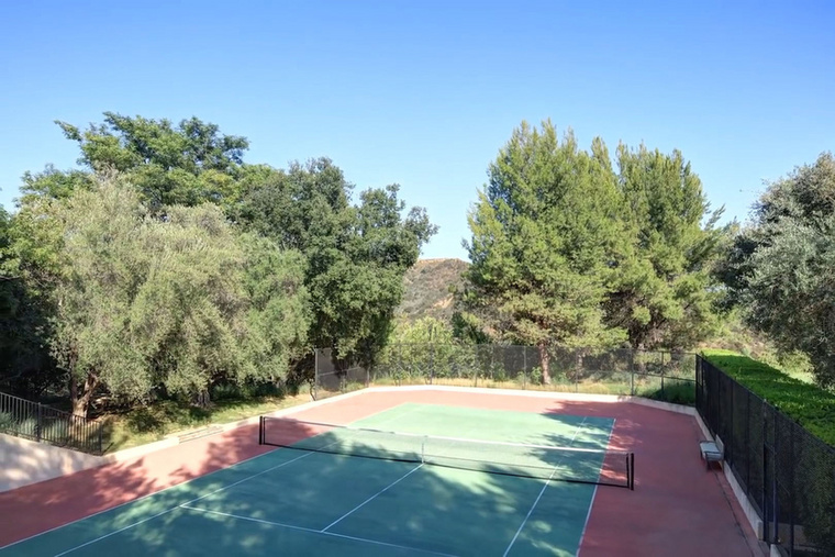 A profi pankrátorból lett színész otthonában egy hatalmas edzőterem is van, de most a teniszpályáról mutatunk képet.