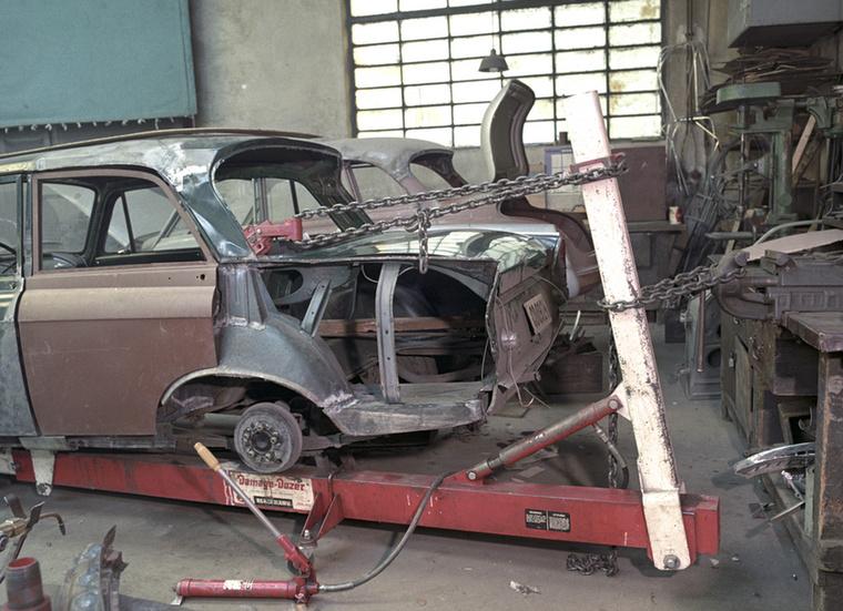 Egy balesetet szenvedett Moszkvics kaszniját próbálják egyengetni egy karosszériás műhelyben
