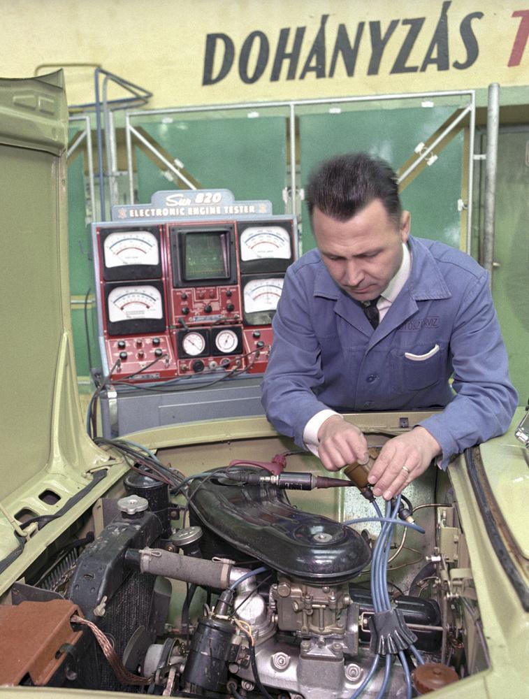 Éppen egy személyautó gyújtását ellenőrzi az autószerelő egy szervizben