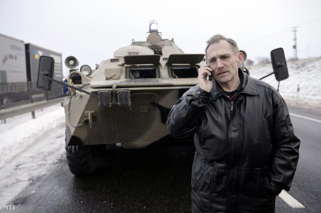 Pintér Sándor belügyminiszter egy páncélozott jármű előtt telefonál az M1-es autópályán Bábolna mellett.