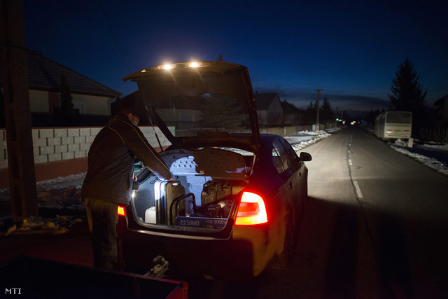 A paszabi önkormányzat munkatársa üzemanyagkannákat tesz autója csomagtartójába egy aggregátor mellé