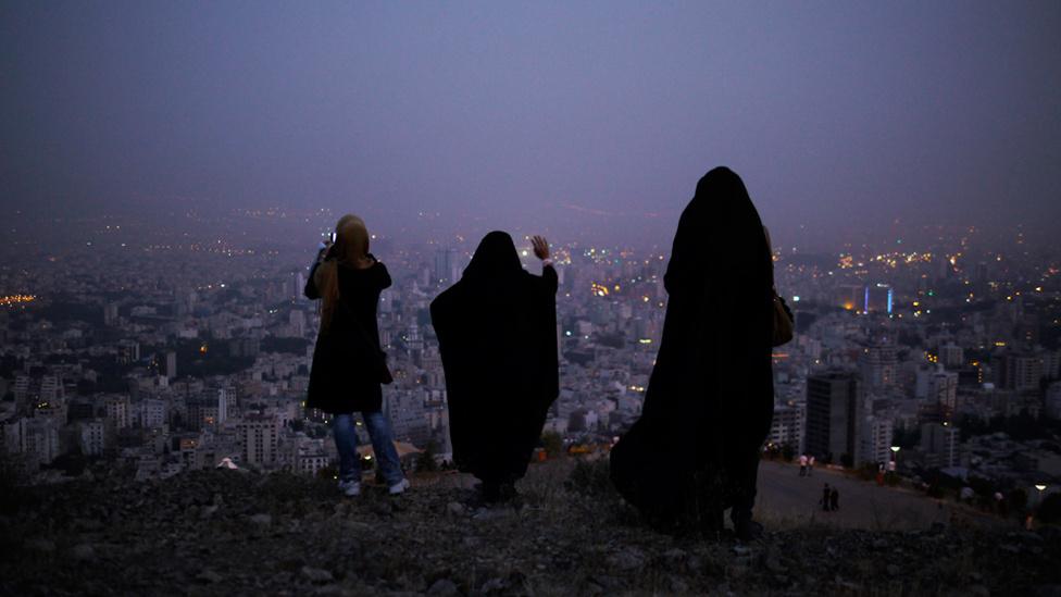 Iráni asszonyok állnak alkonyatkor a Teherán fölötti hegyekben. A zárt ruházat, köztük a fejkendők viselete kötelezők a nőknek az iszlám köztársaságban, habár a fiatalok között mindig megjelennek tavasszal a reformtörekvések. 2010-ben egy magas rangú pap arra vezette vissza a földrengéseket Iránban, hogy a nők sokszor túl sokat mutatnak a férfiaknak.