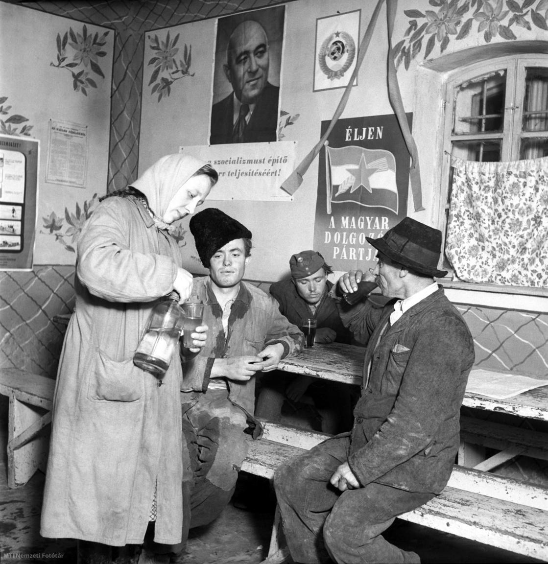 1951. március.Szódát tölt a kiszolgálóegy vendég poharába egy vidéki földműves-szövetkezet italboltjában, amelynek falát Rákosi-kép és MDP-plakát (Magyar Dolgozók Pártja) dekorálja. A felvétel készítésének helyszíne és pontos dátuma ismeretlen.Az ötvenes évek elején a falvak ellátása a területi alapon szervezett földműves-szövetkezetek (az áfészek jogelődjei) feladata lett, amelyek eszközei kezdetben túlnyomórészt az államosítással párhuzamosan átszervezett szövetkezeti kereskedelemből származtak. Az összevonások következtében egy faluban csak egy földműves-szövetkezet működött, s gyakori volt a szomszédos települések szövetkezeteinek összevonása is. E szervezetek irányítását a Szövosz (Szövetkezetek Országos Szövetsége) végezte. A Szövosz ugyan elvileg társadalmi szervezet volt, gyakorlatilag azonban egy középirányító szervezetre jellemző feladatokat látott el