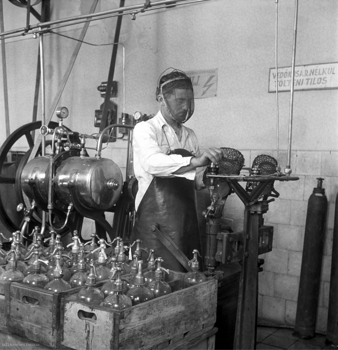Bács-Kiskun megye, 1954. június 5. Gulyás János szódásüvegek töltését végzi egy Bács-Kiskun megyei földműves-szövetkezet szikvízüzemében. A felvétel készítésének pontos helyszíne ismeretlen