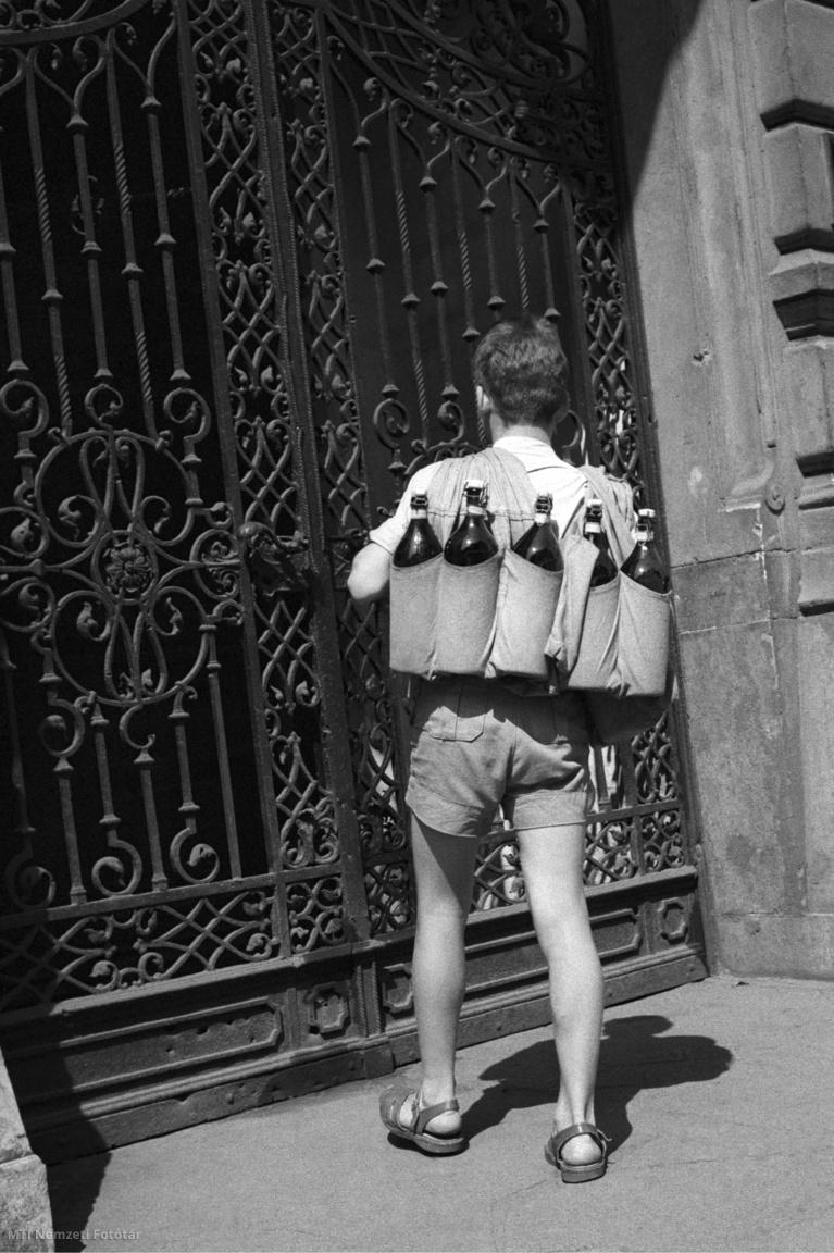 """Budapest, 1960. augusztus 2. Szikvizet szállít házhoz egy férfi a Közértből a szomszédos Bem rakparti irodaházba. A Közért egyik elődje az 1911-ben a drágaság megfékezésére létrehozott Budapest Székesfőváros Községi Élelmiszerárusító Üzem volt, amelynek ötven boltjában olcsó, jó minőségű húsárut kínált a főváros lakóinak. Az üzemet 1948-ban vonták össze másik három kereskedelmi vállalattal, 1948. május 7-én jelent meg kormányrendelet a Községi Élelmiszerkereskedelmi Rt. létrehozásáról. A Közért május 15-én kezdte meg működését. Feladatának a közellátás biztosítását jelölték meg, a részvénytársaságból a következő évben lett """"nemzeti vállalat"""""""