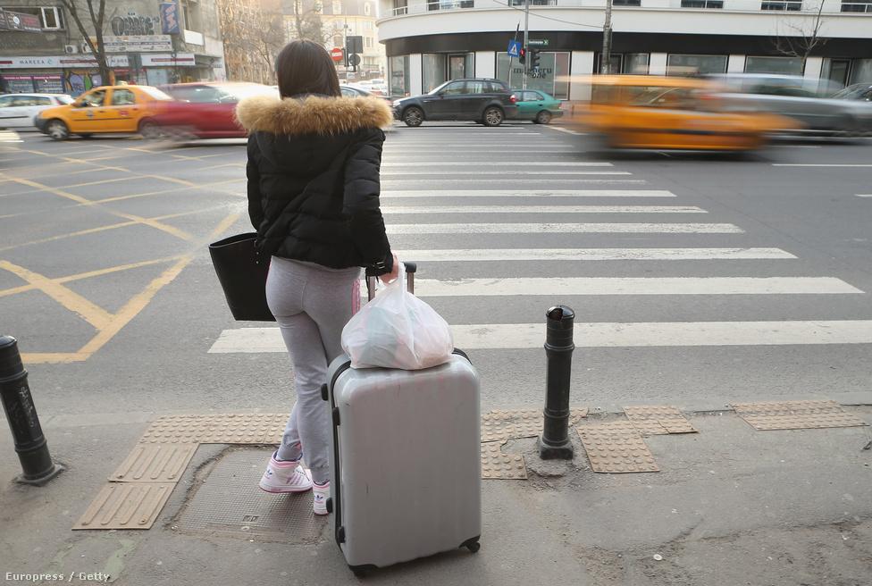 Fiatal nő vár az átkelésre Bukarestben.  A célországok megváltozásával most egy időszakos lassulás tapasztalható, az elmúlt években visszaesett a kivándorlók száma.