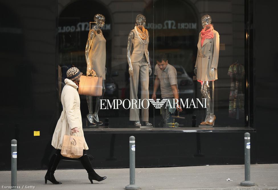 Divatosan öltözött nő sétál egy rendezés alatt álló Armani üzlet előtt Bukarestben.  Komoly társadalmi különbségek alakultak ki a szegényebb és gazdagabb rétegek között, a határnyitástól való félelem egyik oka, hogy így még többen indulnának külföldre szerencsét próbálni.