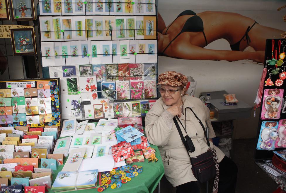 Egy asszony képeslapokat árul a Piaţa Romanănál.  Nyugat-európai és észak-amerikai országokban összesen hárommillió román él.