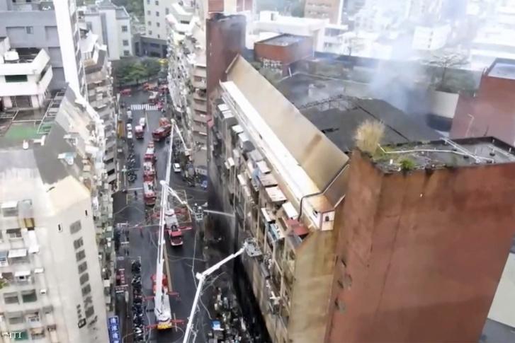 Tűzoltók küzdenek a lángok megfékezésén miután tűz ütött ki egy tizenhárom emeletes épületben a dél-tajvani Kaohsziung városban 2021. október 14-én.