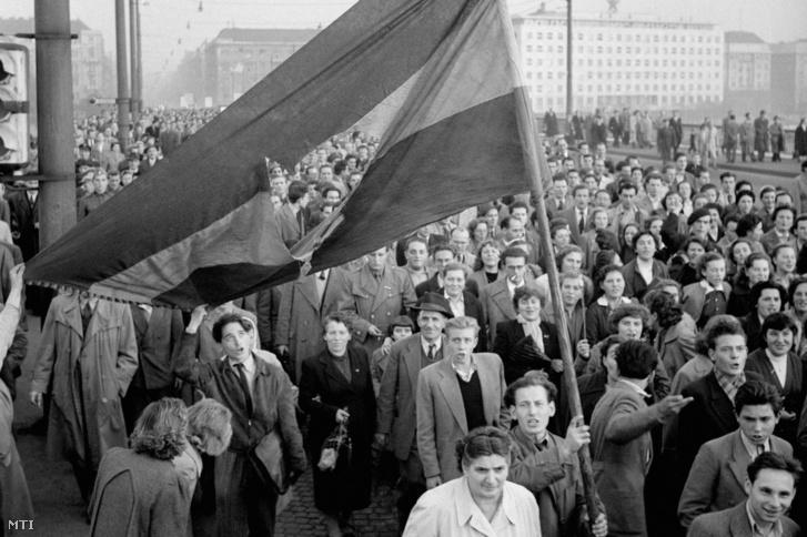 Lyukas nemzetiszínű zászlóval vonul a tömeg a Margit hídon át a Bem-szoborhoz.