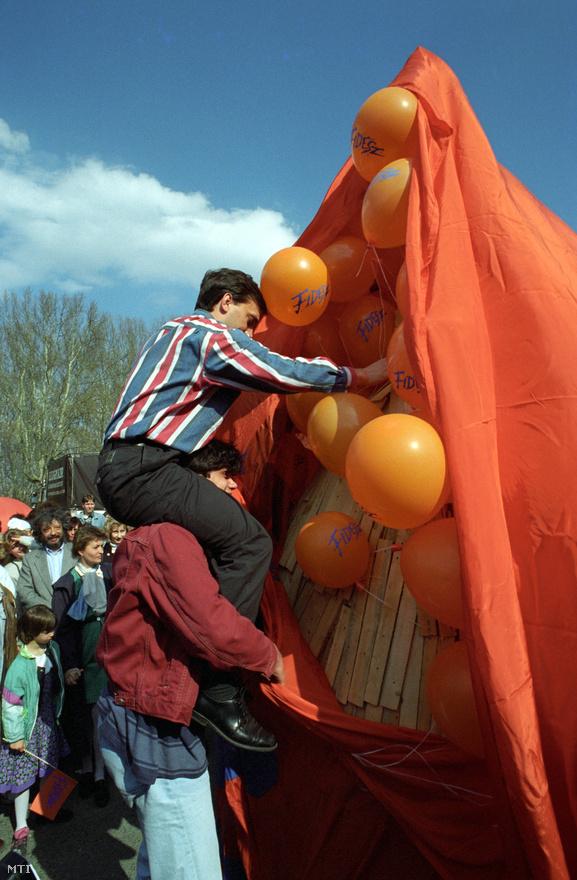 """A kultikus csíkos ingét viselő Orbán Viktor Deutsch Tamás nyakából nyújtózva leplezi le a Fidesz 1994-es születésnapjára készült """"Fülinapi Fanyulat"""". A pártnak azonban ekkor nem volt túl sok oka az ünneplésre: miután 1992-ben még toronymagasan vezette a közvélemény-kutatásokat, az 1994 májusában tartott választásokon alig sikerült megszereznie a mandátumok öt százalékát. A kudarc megerősítette a párt vezetését abban, hogy számukra csak a jobboldalon terem babér."""