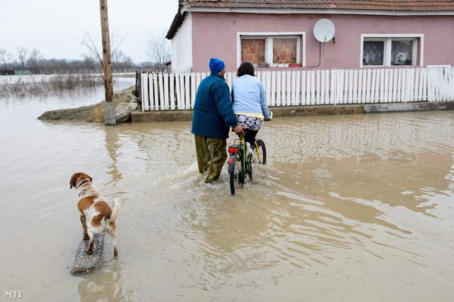 Helyi lakosok az ipolytarnóci Rákóczi úton miután a kiáradt Ipoly folyó hét portát öntött el a településen.