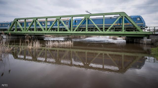 Egy vonat halad át a Hortobágy-Berettyó felett Püspökladány közelében. A folyó ezen szakaszán másodfokú a készültség.