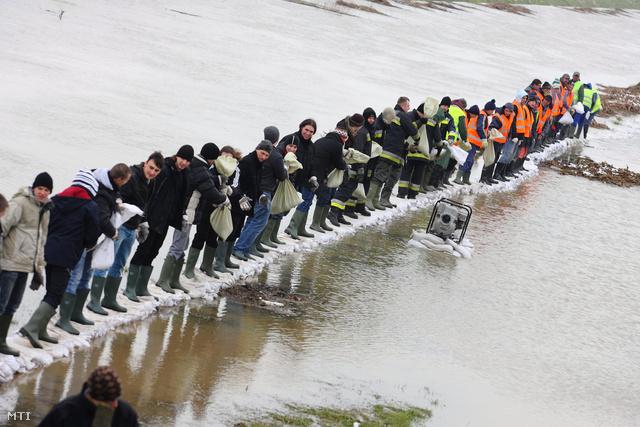 Tűzoltók, önkéntesek és diákok pakolnak homokzsákokat Nagykanizsán, 2013. április 3-án