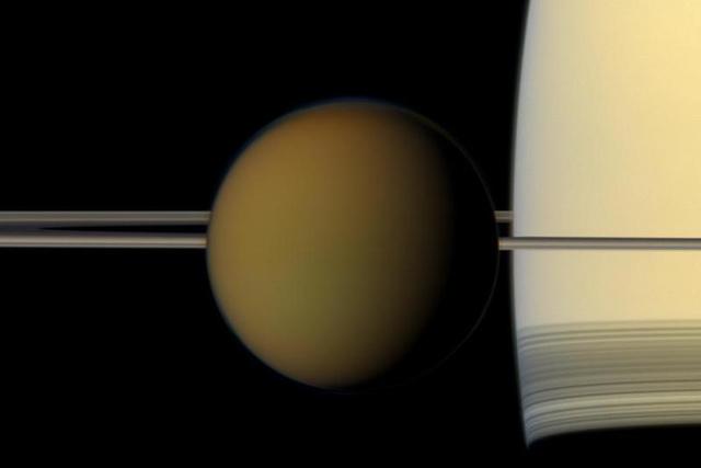 A Szaturnusz legnagyobb holdja, a Titán elhalad a bolygó gyűrűrendszere előtt a Cassini űrszonda felvételén