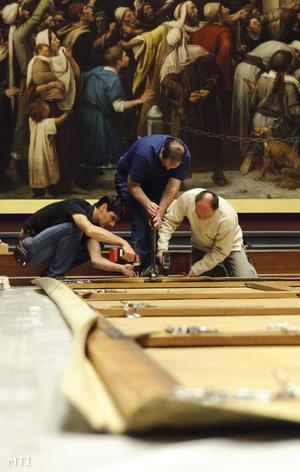 A Déri Múzeum munkatársai keretre feszítik Munkácsy Golgota című festményét