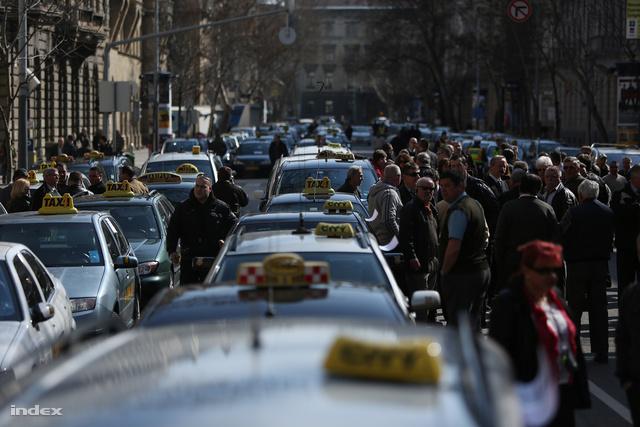 Közel száz taxis gyűlt már össze az Alkotmány utcában,akik a fővárosi közgyűlés elé beterjesztett taxisrendelet tervezete ellen tiltakoznak.