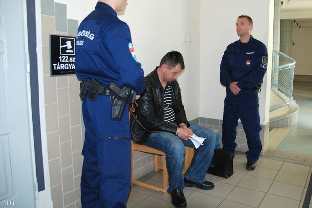 A kényszervallatás és halált okozó testi sértés gyanúja miatt őrizetbe vett két izsáki rendőr egyike várakozik az előzetes letartóztatásról döntő ülés előtt a Kecskeméti Városi Bíróság folyosóján.