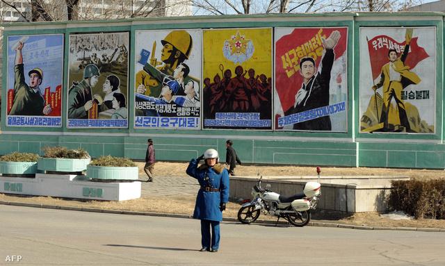 Észak-koreai rendőr állami propaganda plakátok előtt
