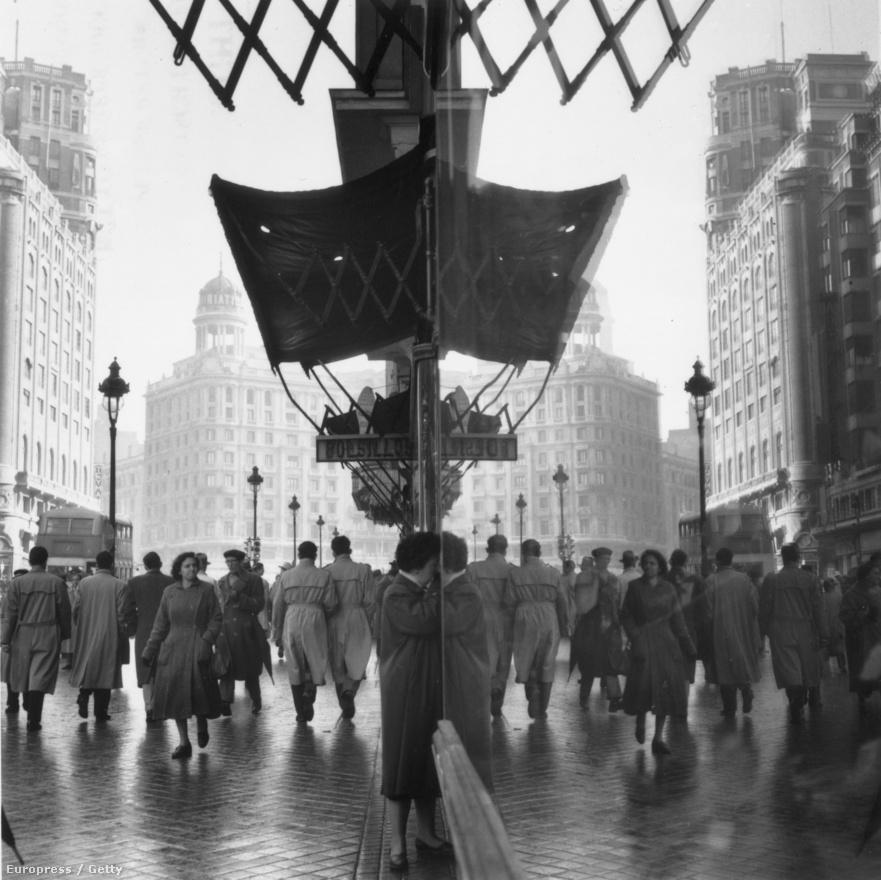 Egy zsúfolt madridi utca és tükörképe egy üzlet kirakatában (1956).