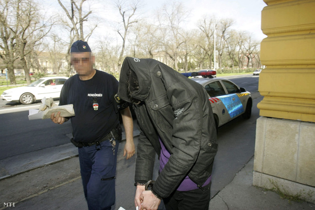 Rendőr vezeti elő 2013. április 19-én a székesfehérvári bíróság épületébe az előzetes letartóztatásról döntő ülésre azt a férfit, aki a gyanú szerint feleségével halálra éheztette gyermekét Agárdon.