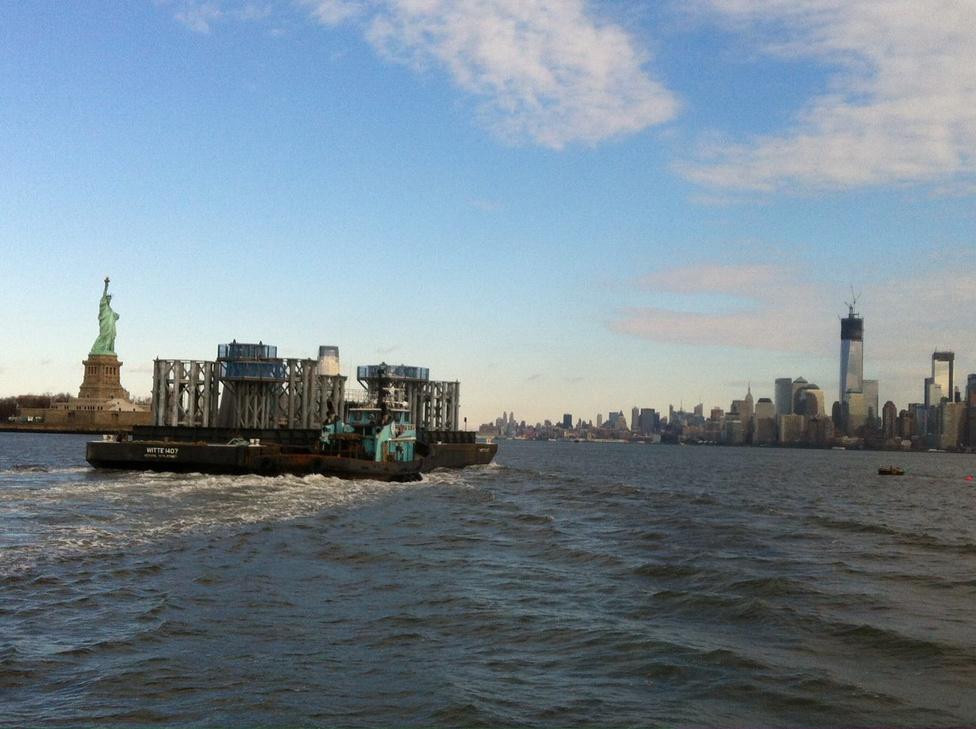 New York két ikonikus látványossága egy képen: a Szabadság-szobor mellett úsztatják el éppen az új WTC néhány szerkezeti elemét az építkezéshez.