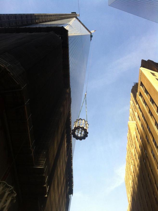 2012. december, a csúcsdísz egyik darabját emelik fel a felhőkarcoló tetejére.