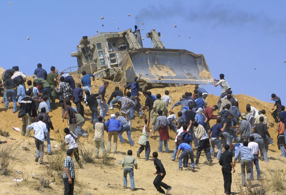 A közeledés ellenére nem sikerült tartós megoldást elérni a következő évtizedekben sem a palesztin-izraeli kérdésben, a telepbővítések pedig folytatódtak. Palesztin fiatalok köveket dobálnak izraeli katonai buldózerek ellen Beit Lahiánál a Gázai övezet északi részén 2004. április 22-én.