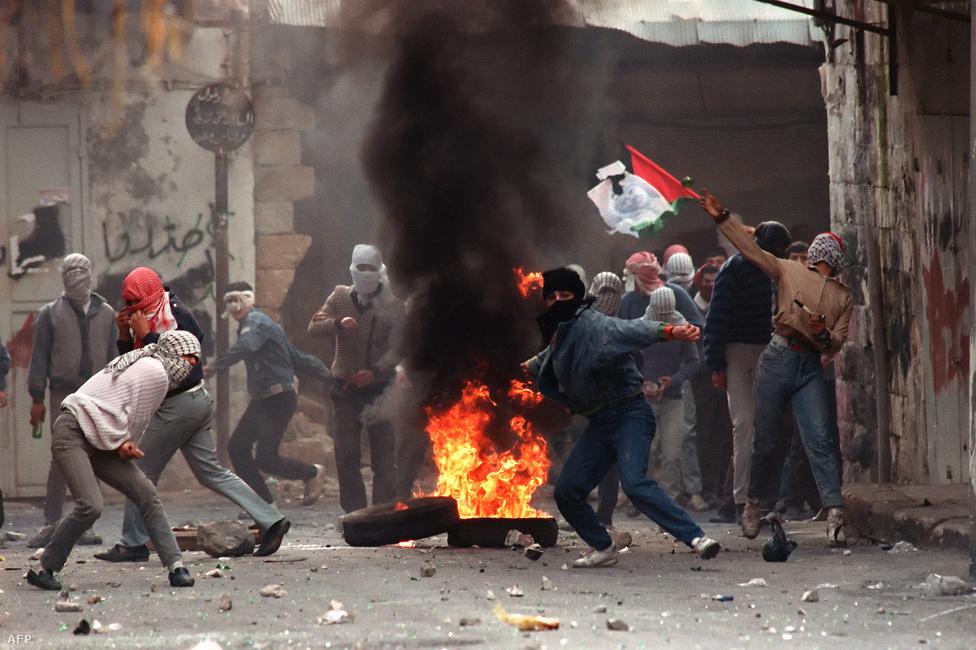 Palesztin tüntetők kövekkel dobálják 1988. január 29-én Nablusban az izraeli katonákat. Az 1987-ben kirobbant első intifáda (az izraeli megszállás elleni palesztin felkelés) alatt az izraeliek ellen tiltakoztak a palesztinok a megszállt területeken. A Hamász is az első intifáda alatt jött létre. A palesztin csoportokat is egymás ellen fordító erőszakban több ezren haltak meg, míg 1993-ban aláírták az oslói békeegyezményeket.