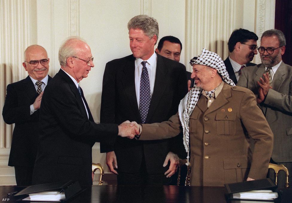 Bill Clinton amerikai elnök közvetítésével kezet fog a hónapokkal később meggyilkolt Jichak Rabin izraeli miniszterelnök és Jasszer Arafat, a PFSZ elnöke 1995. szeptember 28-án a Fehér Házban. A háttérben Hoszni Mubarak egyiptomi elnök és Husszein jordán király figyel. Az 1993-ban aláírt oslói jegyzőkönyvben döntöttek többek között a Palesztin Hatóság felállításáról.