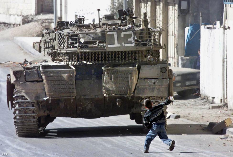 Palesztin fiú dob egy követ egy izraeli tankra a ciszjordániai Hebron városában kirobbant utcai összecsapásokban.