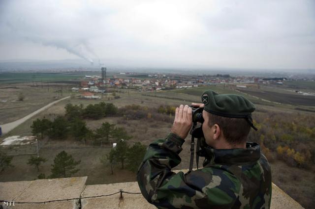 A KFOR magyar katonája távcsővel nézi az Obilich erőművet Pristina határában 2012. november 22-én.