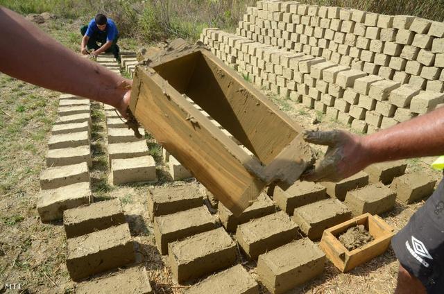 Fából készült sablont (módlát) ad társának egy vályogvető Tiszaigar határában 2012. szeptember 11-én. A Start mintaprogram keretében a településen a közmunkások egy csoportja vályogvetést tanul.