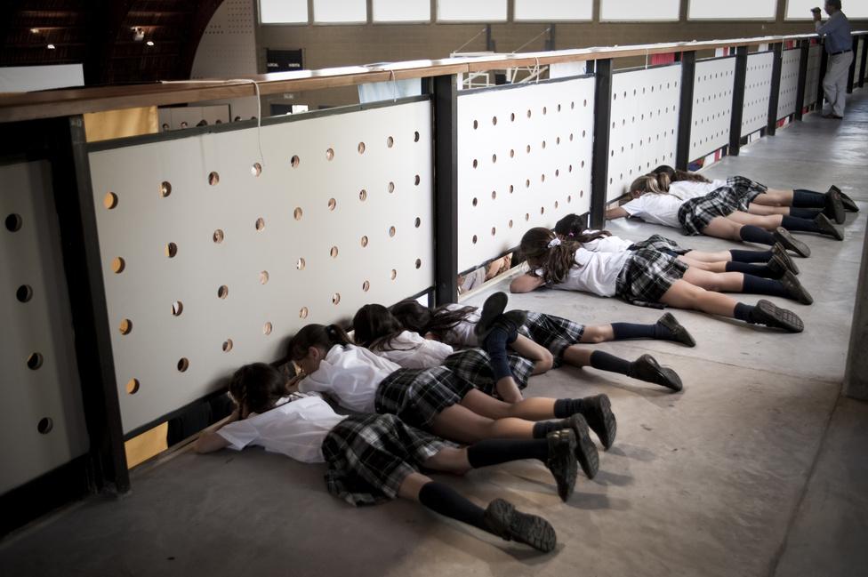 Az alsóbb évesek az emeletről lesik a mintaváros magániskolájának évzáró ünnepségét.