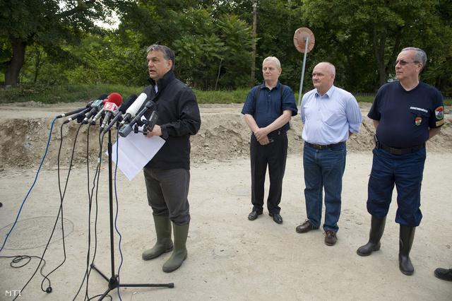 Orbán Viktor tájékoztat, mögötte Tarlós István, Hende Csaba és Bakondi György állnak sorfalat a gáton a Római partnál.