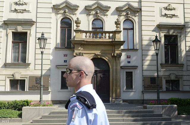 Egy rendőr áll a cseh miniszterelnöki hivatal bejárata előtt Prágában 2013. június 13-án