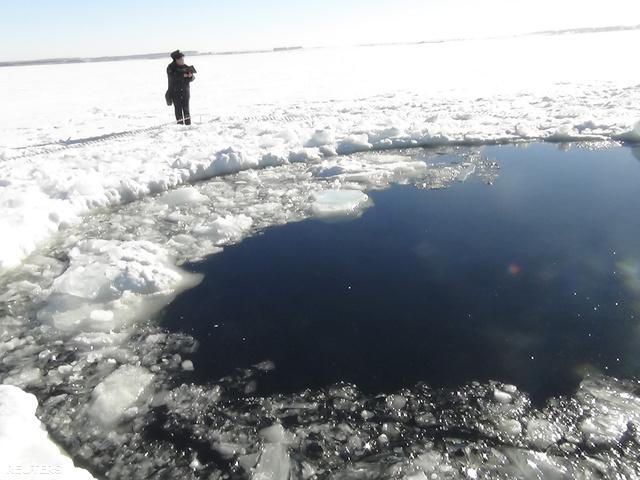 Egy rendőr áll a meteor ütötte lék mellett a Cseljabinszktól 80 kilométerre  nyugatra lévő Csebarkul tavon. A lék átmérője nagyjából nyolc méter.
