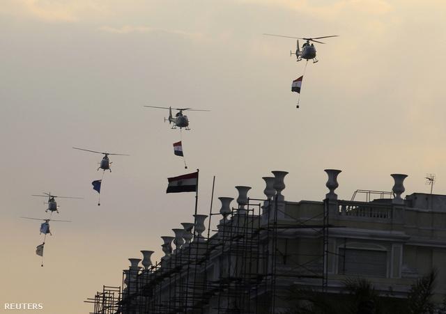 Egyiptomi katonai helikopterek nemzeti zászlókkal köröznek a tüntetők felett.