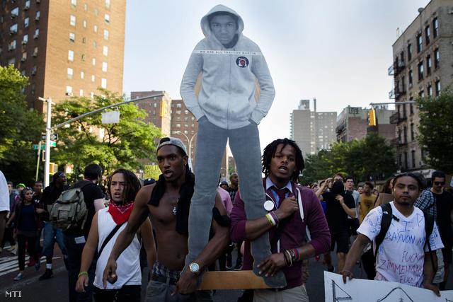 """A Trayvon Martin meggyilkolásával vádolt George Zimmerman bírósági felmentése miatt tiltakoznak tüntetők a New York-i Manhattan negyedben 2013. július 14-én. A 17 éves áldozatot ábrázoló kép feliratának jelentése: """"Mindannyian Trayvon Martin vagyunk""""."""