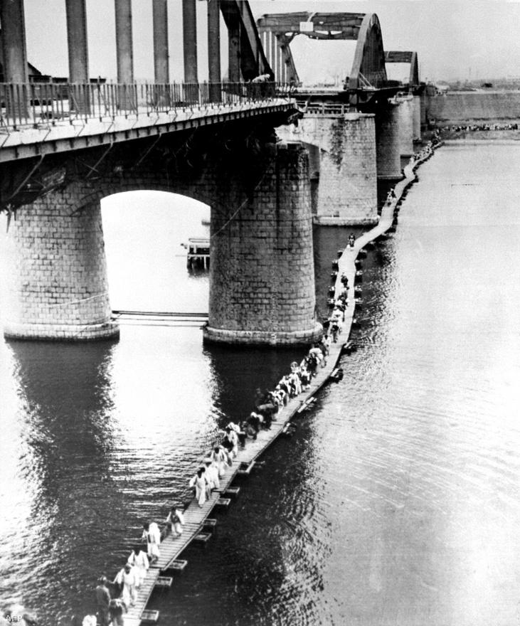Civilek menekülnek a Han folyón át a bombázási zónából.
