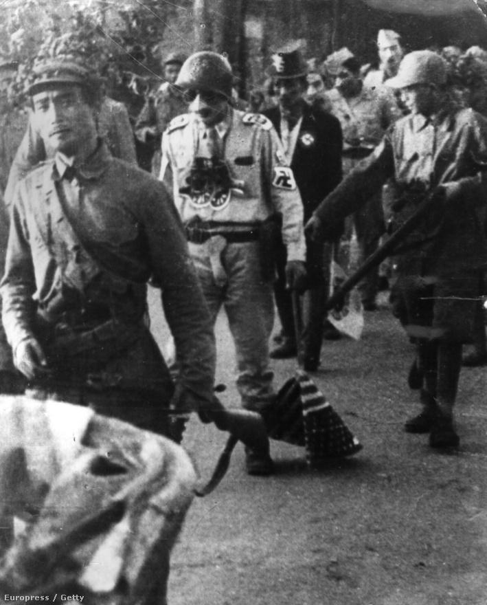 Amerikai hadifoglyok nyilvános megszégyenítése Phenjanban, a képen látható katonának Hitler-bajuszt és horogkeresztes karszalagot viselve, az amerikai zászlót a földön húzva kell végigvonulnia a rajta gúnyolódó északiak között.